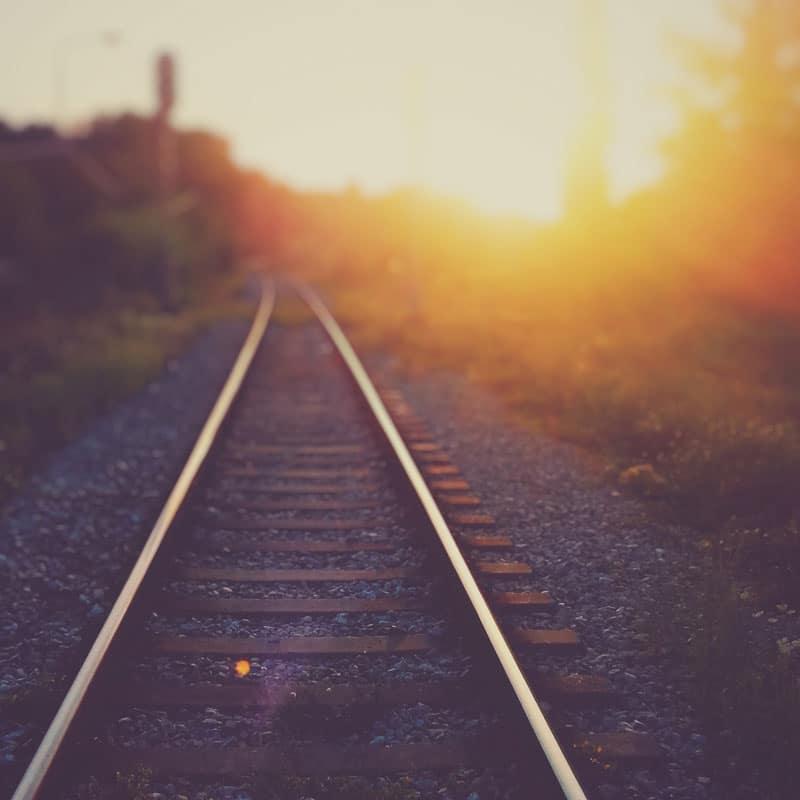 Vue d'une rail de chemin de fer menant vers un soleil couchant.