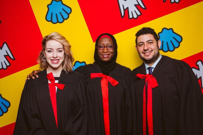 3 diplômés en toges souriant sur fond du drapeau de l'Université Laval