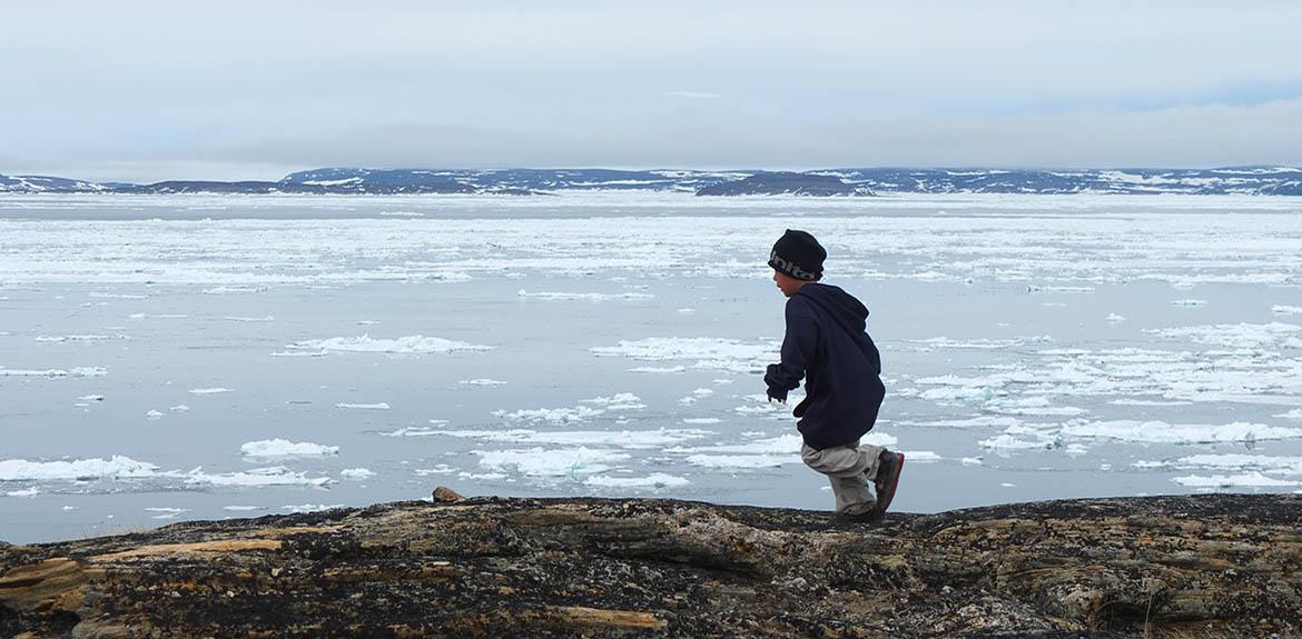 A young Inuk runs on a riverbank.