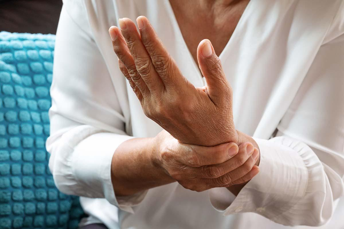 A woman massages her wrist to relieve chronic pain.