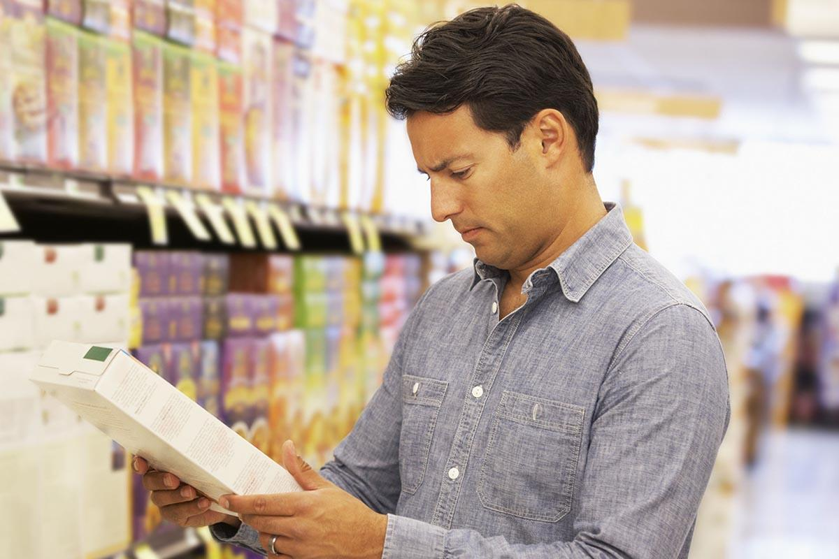 A man reads the nutrition information on the back of a cereal box in a grocery aisle.